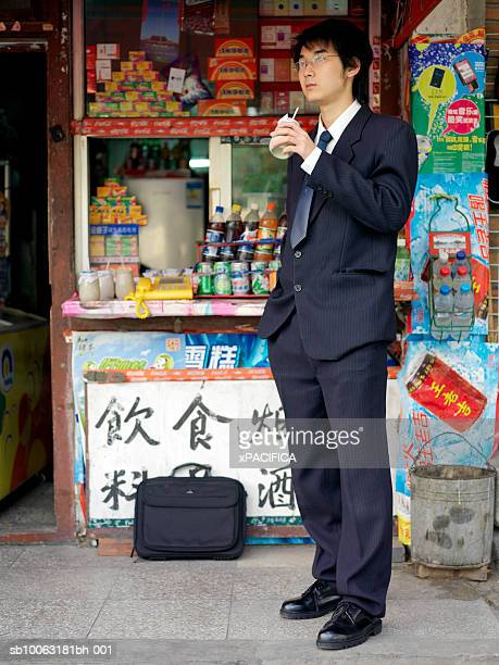 China, Beijing, young business man drinking in front of kiosk