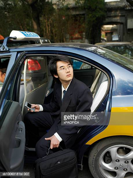 China, Beijing, young business man in taxi, holding briefcase and phone, looking up