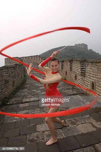 China, Beijing, Young woman dancing at Great wall of China