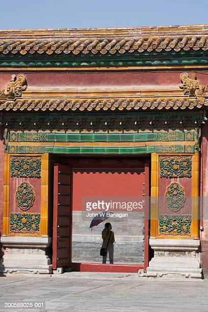 China, Beijing, young woman with umbrella inside Forbidden City