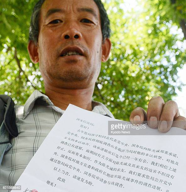 BEIJING China Chen Guangfu older brother of Chinese human rights activist Chen Guangcheng shows a petition before submitting it in Beijing on June 19...