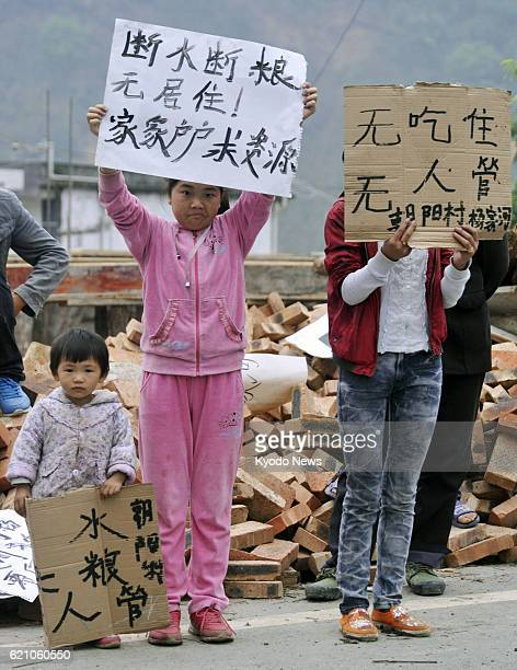 YA'AN China Children hold signboards reading 'No water no food' 'No place to live' and 'Nobody cares' in the Lushan county area of Ya'an in the...