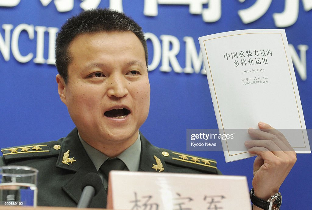BEIJING, China - Chinese Defense Ministry spokesman Yang Yujun holds up a copy of the country's defense white paper at a press conference in Beijing on April 16, 2013.