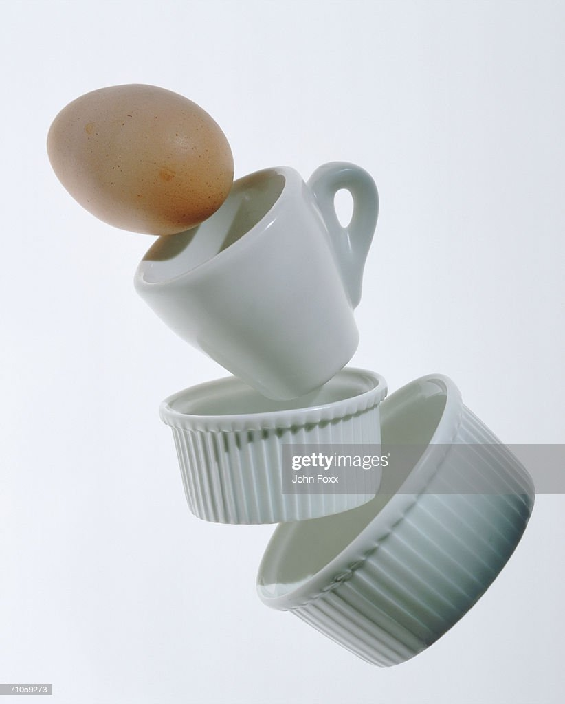 China cup and egg on white background, close-up : Stock Photo