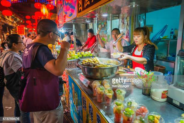 China customers and vendors at night market food stalls Beijing