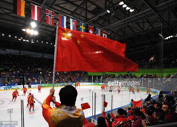 A China fan waves the natinal flag at the start of the Women's Ice Hockey preliminary game between China against Russia at the UBC Thunderbird Arena...