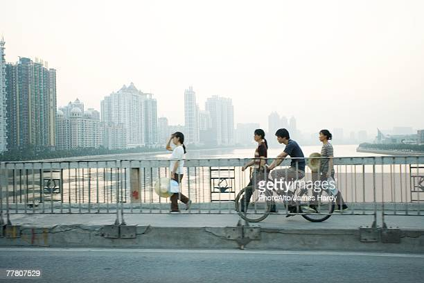 China, Guangdong Province, Guangzhou, cyclists and pedestrians crossing bridge, skyscrapers in distance