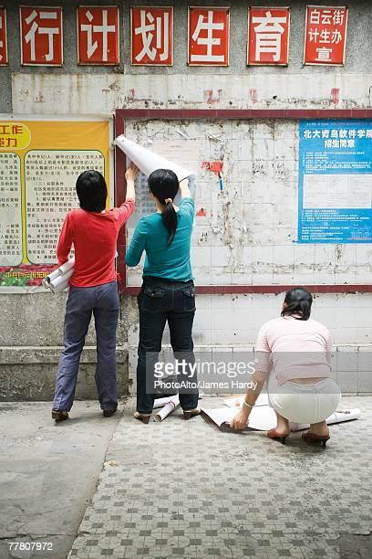 China, Guangdong Province, Guangzhou, young women hanging posters on wall