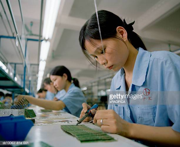 China, Guangdong, uniformed workers at electronic factory