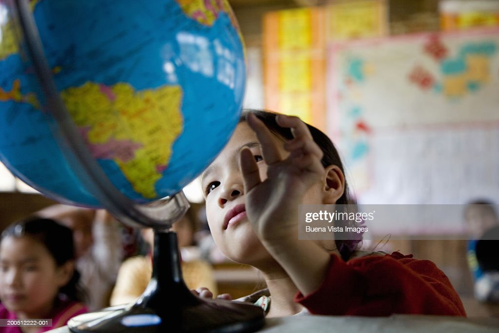 China, Guangxi Province, girl (6-9) looking at globe in class : Stockfoto