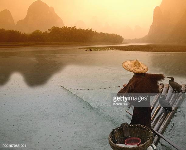 China, Guangxi, Yangshuo, fisherman casting net from bamboo raft, dawn