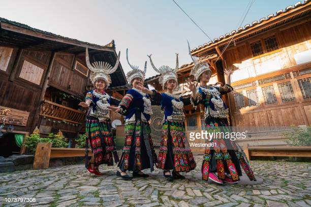 china, guizhou, miao women wearing traditional dresses and headdresses posing on village square - chinese ethnicity ストックフォトと画像