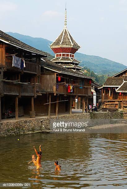 China, Guizhou province, Zhaoxing, Dong children (10-12) playing in river