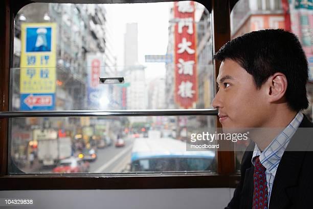 China, Hong Kong, business man sitting in double Decker tram, side view