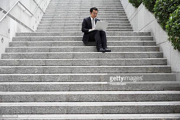 China, Hong Kong, business man sitting on steps using laptop, low angle view