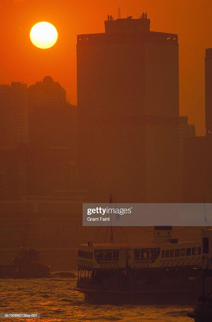 China, Hong Kong, ferry crossing harbor at sunset : Stockfoto