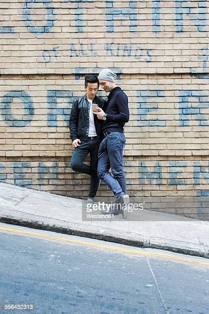 China, Hong Kong, gay couple at house wall looking on cell phone