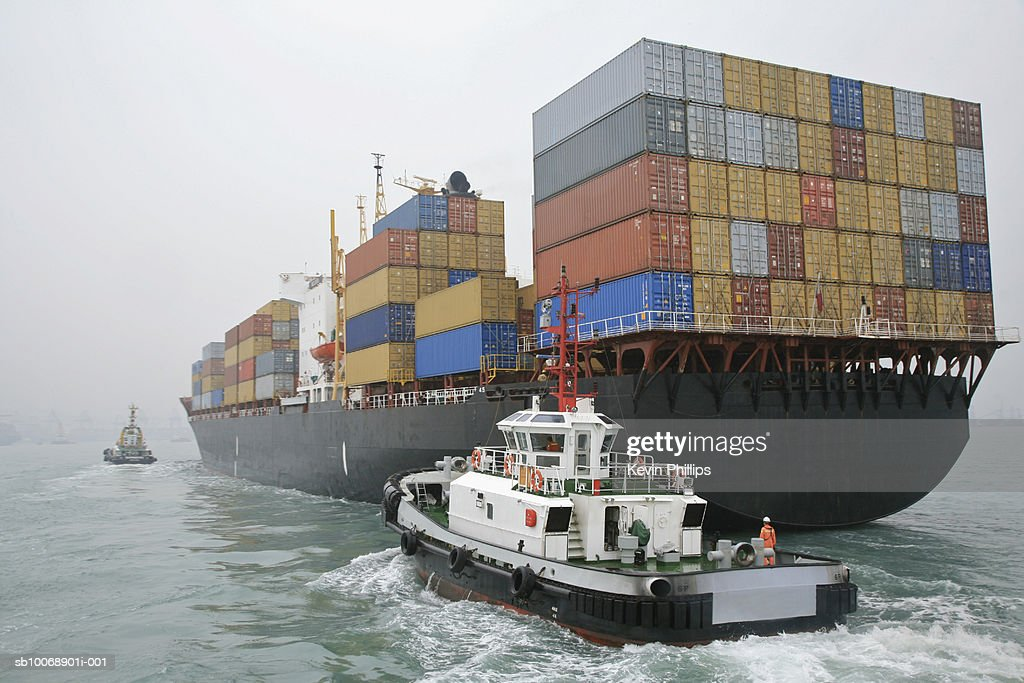 China, Hong Kong Harbor, tugboat sailing alongside container ship : Stock Photo