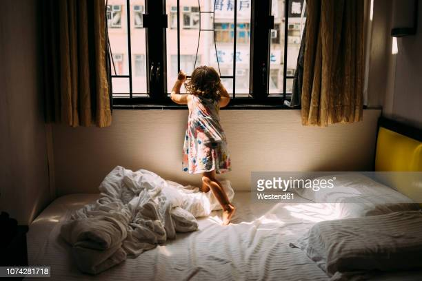 China, Hong Kong, Mong Kok, back view of little girl standing barefoot on bed looking out of window
