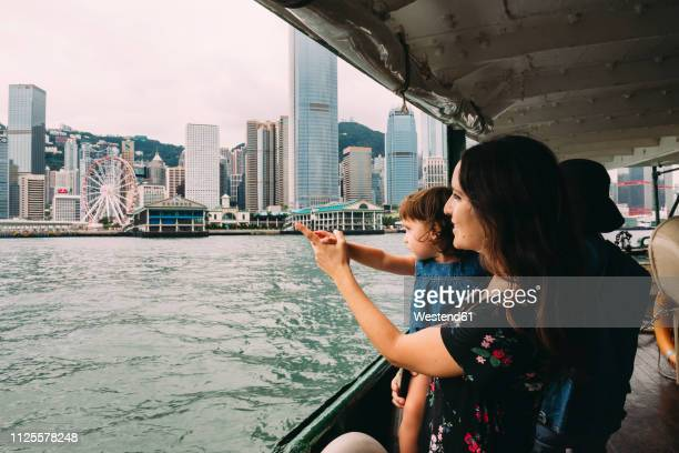 china, hong kong, mother and little daughter crossing the river by ferry from kowloon to hong kong island - passagier wasserfahrzeug stock-fotos und bilder