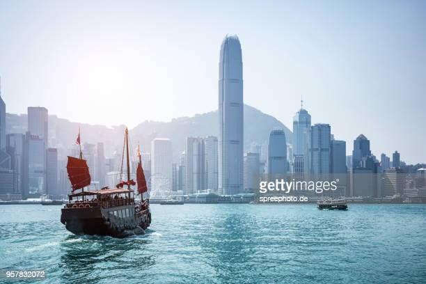china, hong kong victoria harbour with historic sailboat and skyline - hong kong stock pictures, royalty-free photos & images
