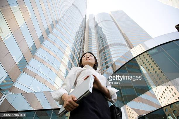 China, Hong Kong, young businesswoman in front of office building