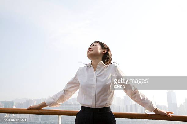 China, Hong Kong, young woman standing on balcony, looking up