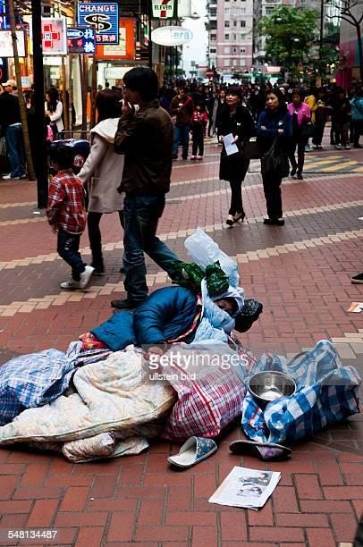 China Hongkong Wan Chai female beggar is lying in a pedestrian zone in Causeway Bay