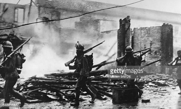 China Hubei Wuhan japanese soldiers in Hankau passing by burning ruins of houses Oktober 1938 Photographer Weltbild Vintage property of ullstein bild