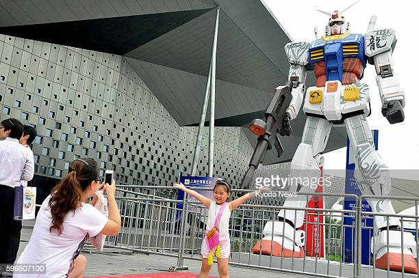 SHANGHAI China Japanese toy maker Bandai Co sets up a 6metertall statue of Mobile Suit Gundam from a popular Japanese animation series at a comics...