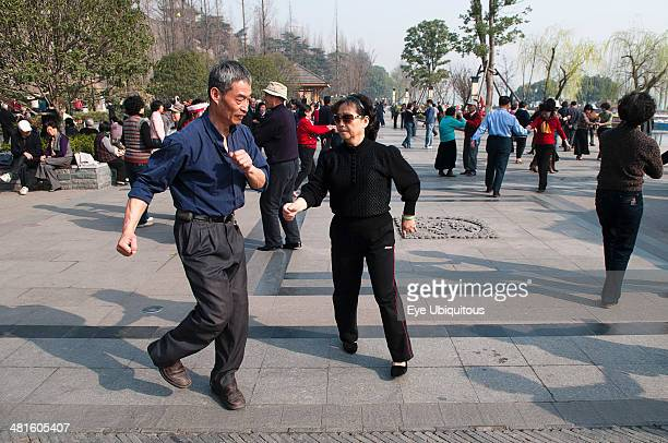 China Jiangsu Nanjing Retired couples dancing beneath the Ming city wall at Xuanwu Lake Park Couple in foreground swinging arms in modern dance