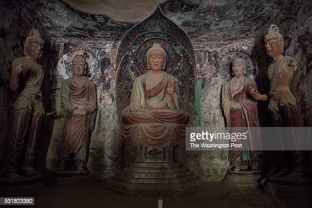 DUNHUANG GANSU China May 3rd 2016 In a Mogao cave lit by a the flashlight of a guide a Buddha statue surrounded by disciples dating from Tang Dynasty...