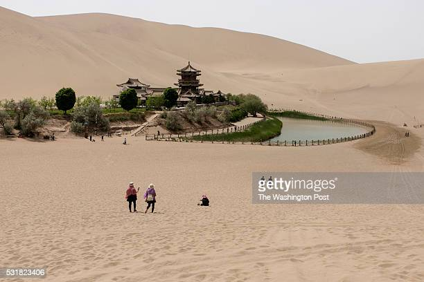 China - May 3rd, 2016 Tourists visiting the Crescent Lake in Dunhuang, one of the city major tourist site along with the Mogao caves. Photo by Gilles...