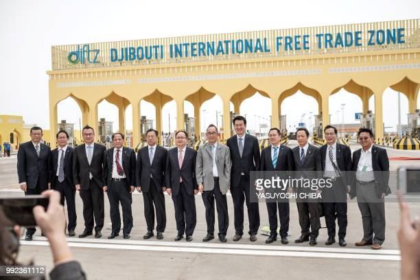 China Merchants Group members take pictures at the main gate of Djibouti International Free Trade Zone after the inauguration ceremony in Djibouti on...
