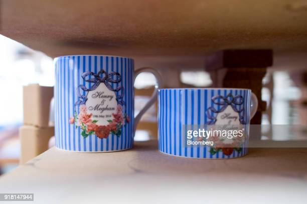A china mug and teacup to commemorate the wedding between Henry Windsor and Meghan Markle stand on a kiln rack at Halcyon Days Ltd's factory in...