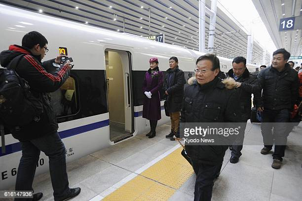 BEIJING China Passengers get aboard a new highspeed train at Beijing West station on Dec 26 as the world's longest highspeed train line298 kilometers...