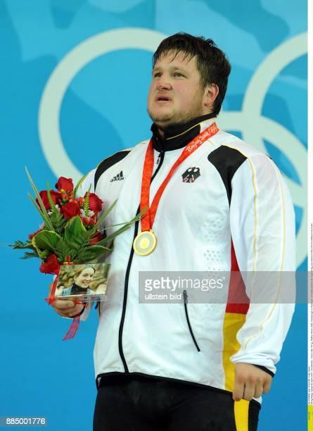 Olympische Spiele 2008 Gewichtheben Klasse ueber 105 kg Matthias Steiner Olympiasieger im Zweikampf mit Goldmedaille bei der Siegerehrung...