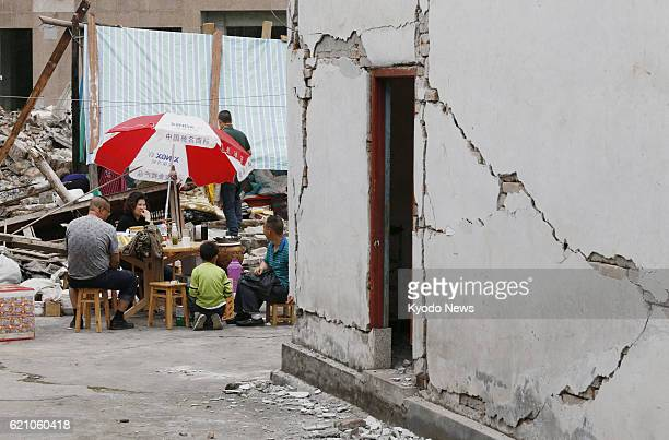 YA'AN China People are seen outside a house bearing cracks in Lushan county in Ya'an in the southwestern Chinese province of Sichuan on April 21...