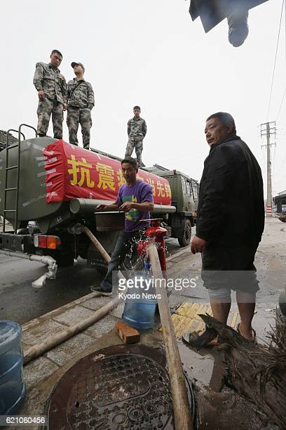 LUSHAN China People get water leaking from an outlet connected to a water truck in central Lushan county in Ya'an in the southwestern Chinese...