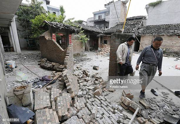 LUSHAN China People walk around damaged houses in central Lushan county in Ya'an in the southwestern Chinese province of Sichuan on April 21...