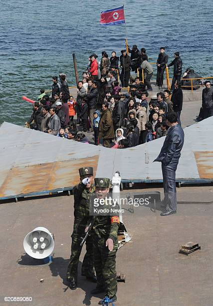 DANDONG China Photo taken from the border city of Dandong in China's Liaoning Province shows North Korean soldiers with guns on a pleasure boat on...