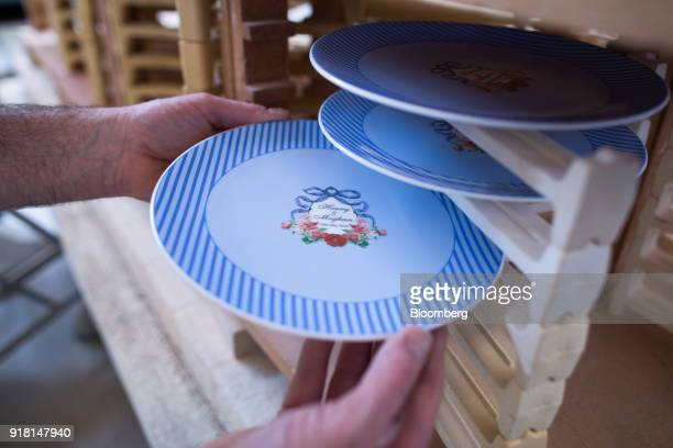 A china plate to commemorate the wedding between Henry Windsor and Meghan Markle is placed onto a kiln rack at Halcyon Days Ltd's factory in...
