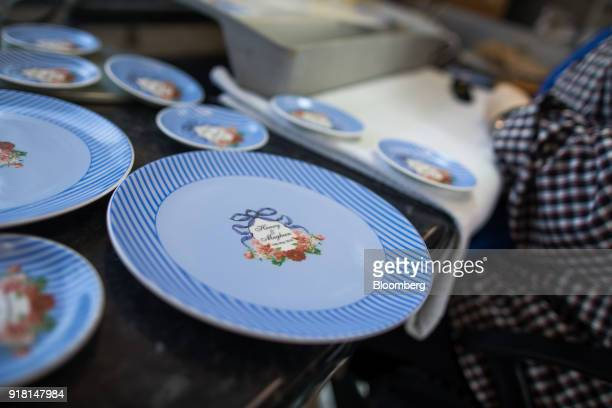China plates to commemorate the wedding between Henry Windsor and Meghan Markle stand next to an employee's workbench at Halcyon Days Ltd's factory...