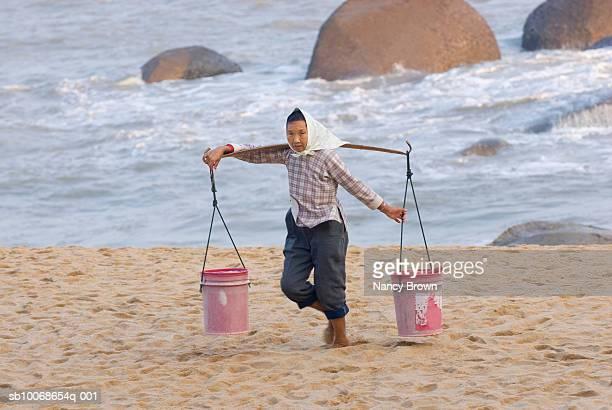 China, Quazhou, woman carrying buckets on beach