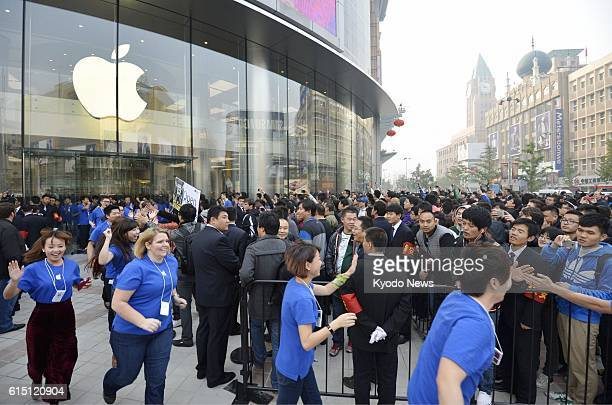 BEIJING China Sales staff at an Apple Store in Beijing run around a crowd who gathered in front of the store to give them a high five on Oct 20 its...