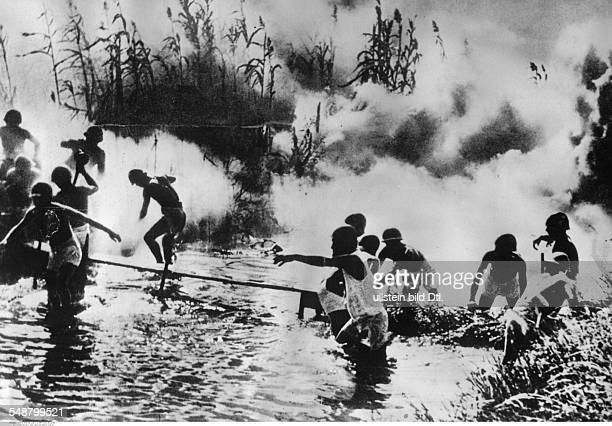 China : Second Sino-Japanese War 1937-1945 Japanese troops crossing a body of water in East China; the bushes at the back had been set on fire by...