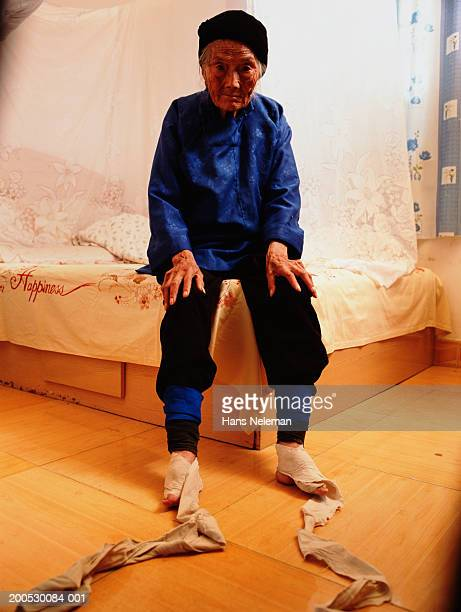 china, senior woman on bed, feet wrappings unbound - foot binding stock pictures, royalty-free photos & images