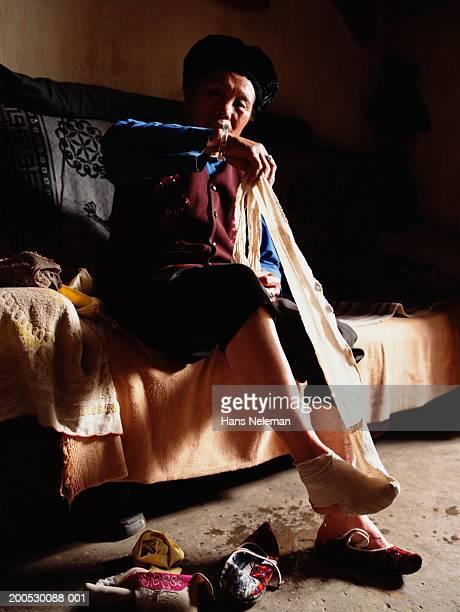 China, senior woman wrapping binding around foot