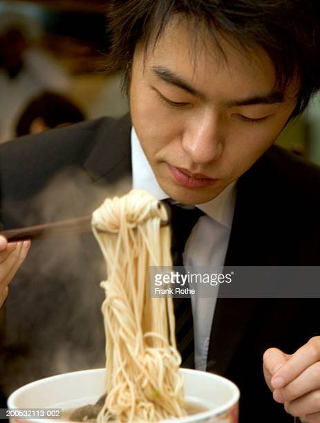 China, Shanghai, businessman eating noodles in restaurant