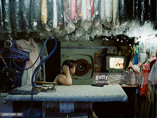 china, shanghai, female dry cleaners owner watching television - dry cleaner stock pictures, royalty-free photos & images